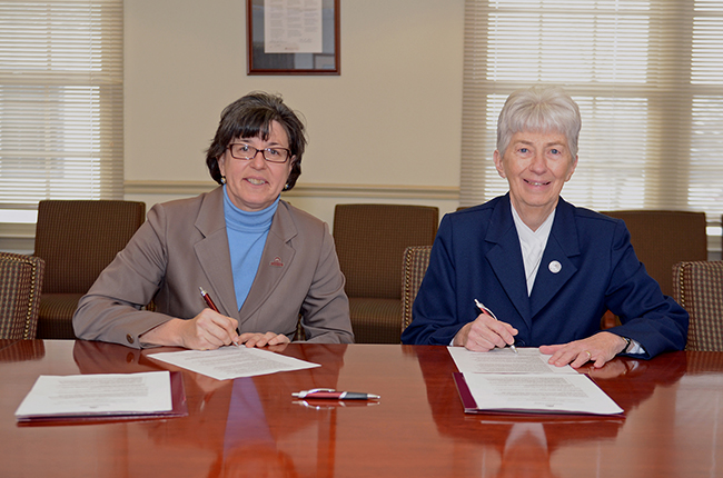 Montgomery County Community College President Dr. Karen A. Stout and Immaculata President Sr. R. Patricia Fadden, IHM, Ed.D., sign the University Center partnership agreement on Feb. 1. Photo by Sandi Yanisko