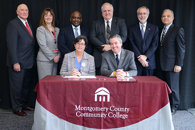 Presidents Dr. Karen A. Stout, MCCC, and John A. Fry, Drexel, sign the University Center partnership agreement. Also pictured (from left) are Tom Freitag, Vice President for Finance and Administration, MCCC; Dr. Victoria Bastecki-Perez, Vice President of Academic Affairs and Provost, MCCC; Dr. Steady Moono, Vice President of West Campus, MCCC; Larry Keiser, Director of Special Projects, School of Education and Goodwin College of Professional Studies, Drexel; William Lynch, Dean, School of Education, Drexel; and KennethMawritz, Assistant Clincal Professor and Interim Program Director, EdD in Educational Leaderhip and Management (Pottstown Cohorts), Drexel. Photo by Sandi Yanisko