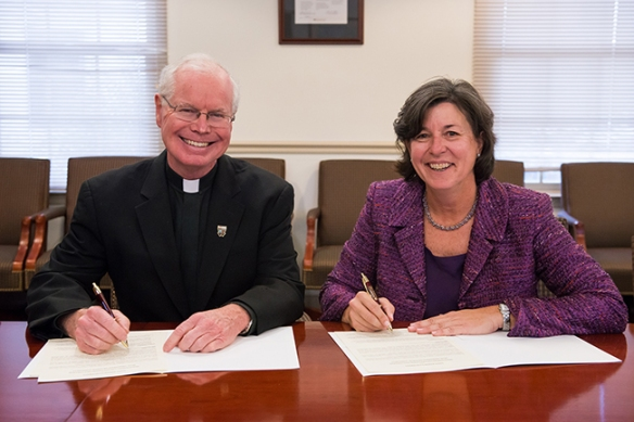 Father C. Kevin Gillespie, president of Saint Joseph's University, and Dr. Karen A. Stout, president of Montgomery County Community College sign a dual admissions transfer agreement on Oct. 23. Photo by Sandi Yanisko