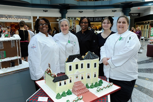 : Montgomery County Community College Culinary Arts Institute (CAI) students Joanne Ratteree and Alana Filipovich (far left and second from right), alumna Kimberly Spruill (center), Chef/Instructor Julia Quay (second from left), and CAI Director/Chef Francine Marz stand with their gingerbread replica of Laurel Hill Mansion. Photo by Anthony Sinagoga.