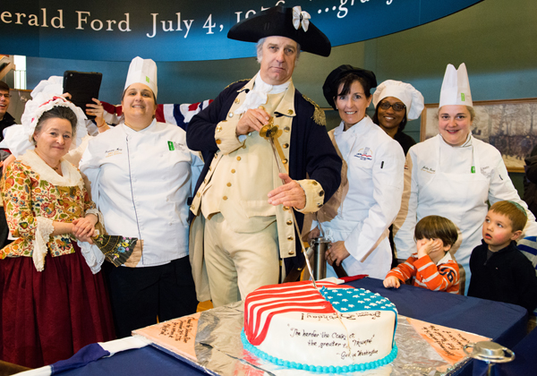 General George Washington prepares to cut his birthday cake, which was prepared by students from the Culinary Arts Institute at Montgomery County Community College. He is joined by CAI student and faculty representatives, as well as by his wife, Martha, on Feb. 17 at Valley Forge National Historical Park. Photo by Sandi Yanisko