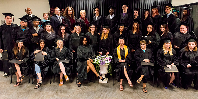GED graduates stand with faculty, staff and community supporters. Photo by Sandi Yanisko