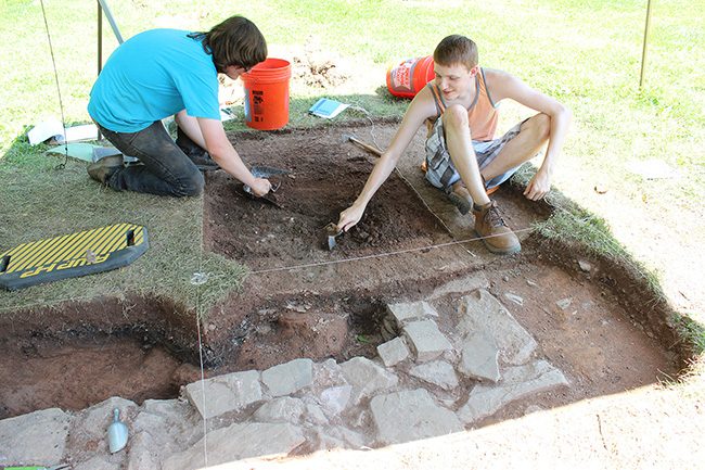 Students Chuck Cannon (left), and Brad James excavate the area around an outbuilding wall last summer. Photo by Alana J. Mauger