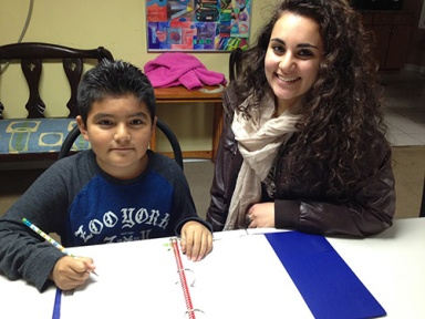 Montgomery County Community College Honors Program student Sussan Saikali works on homework with Kevin, a participants in the Center for Culture, Art, Training, and Education's (CCATE) after school program.