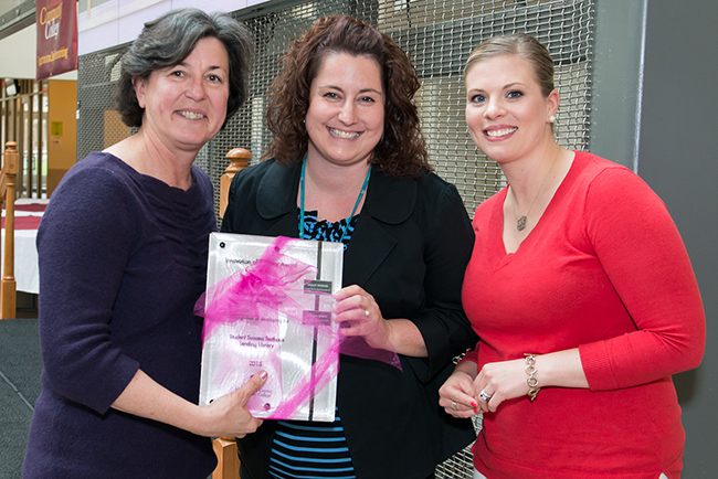 Montgomery County Community College President Dr. Karen A. Stout (left) and Financial Aid Specialist Ashley Smith (right) present Holly Parker, Stowe, financial aid and enrollment generalist, with the 2015 Innovation of the Year award. Photo by Sandi Yanisko